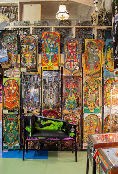The seat is located in front of a wall of pinball playfields