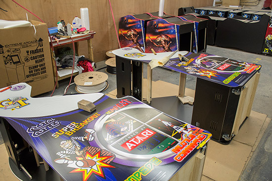 Decals being applied to video game cabinets