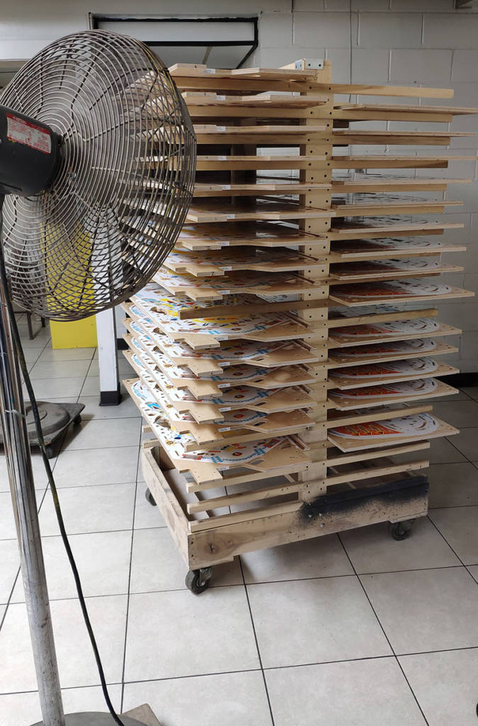 A rack of freshly-printed playfields drying