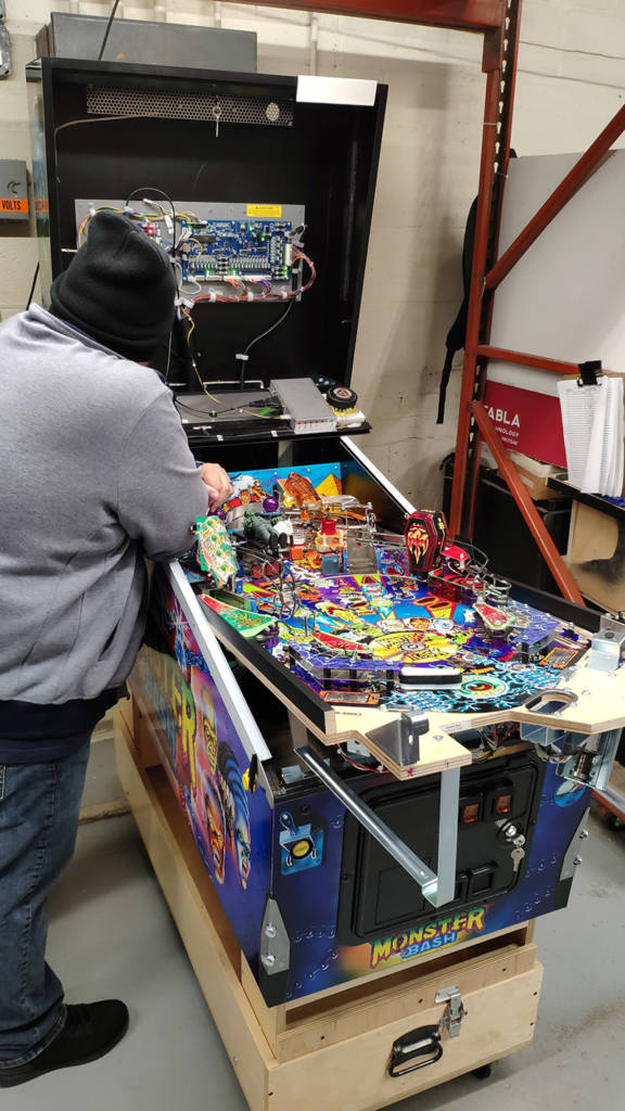 The playfield is installed into the cabinet with the backbox added