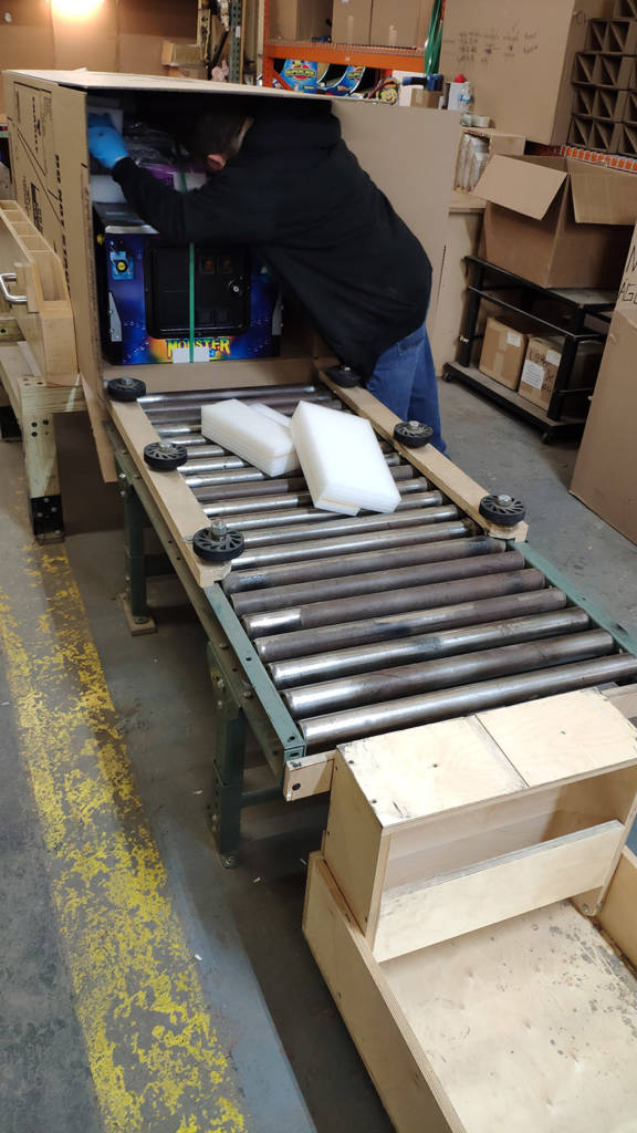 Machines are rolled into their box which is on a special pivot table so it can then be easily stood upright
