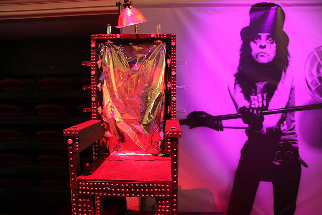 An electric chair prop from Alice Cooper's stage show accompanies the pinball.