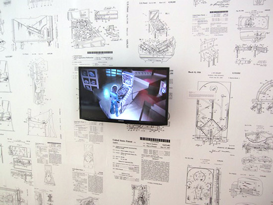A wall with pinball machine diagrams and a video from the movie Tommy