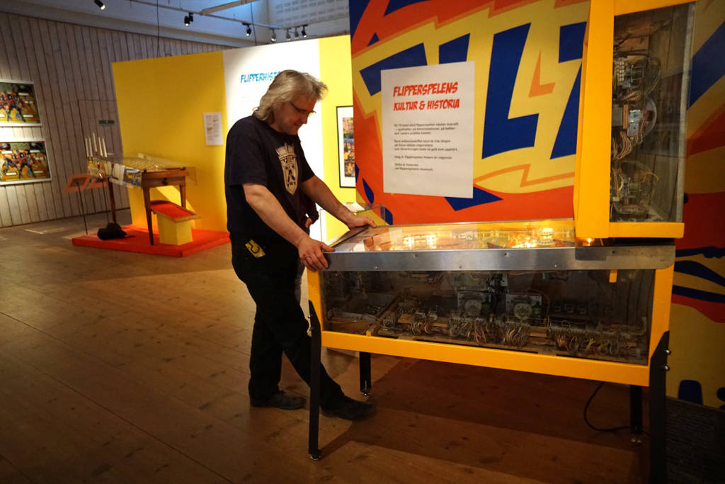 Organiser Claes Johansson plays a credit on the plexiglassed Air Aces with a coinbox filled with old, period-appropriate, Swedish coins. - an example of the attention to detail that runs throughout the exhibit