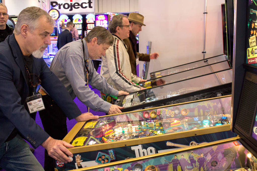 Players enjoying the Stern Pinball machines on the Electrocoin stand