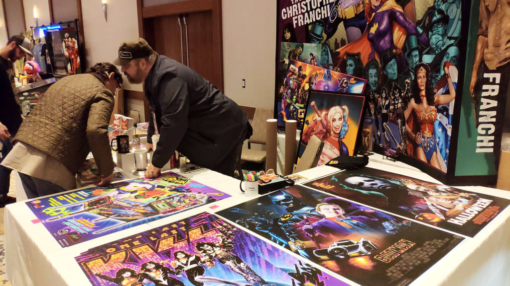 Artist Christopher Franchi at his stand talks to Stern Pinball's George Gomez