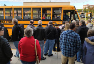 The first bus arrives for the Stern Pinball factory tour