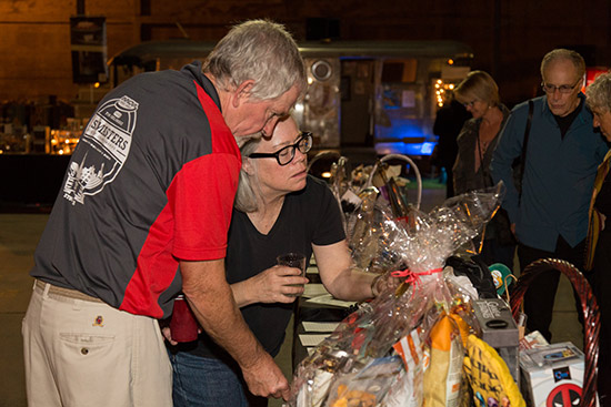 Volunteer couple John and Stephanie Kimball check out the silent auction goodies
