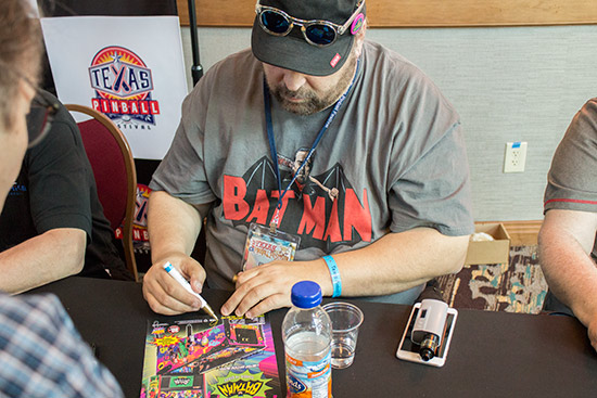 Batman 66 artist Christopher Franchi signs a flyer for the game