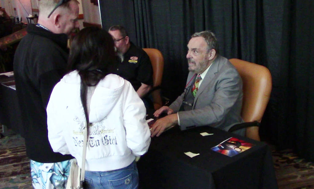John Rhys-Davies at his desk in front of the hall signing autographs and appearing in selfies