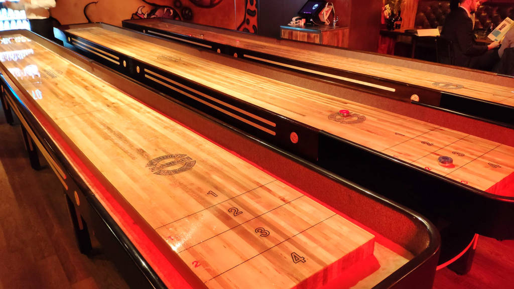 Three shuffleboard tables dominate the far end of the bar