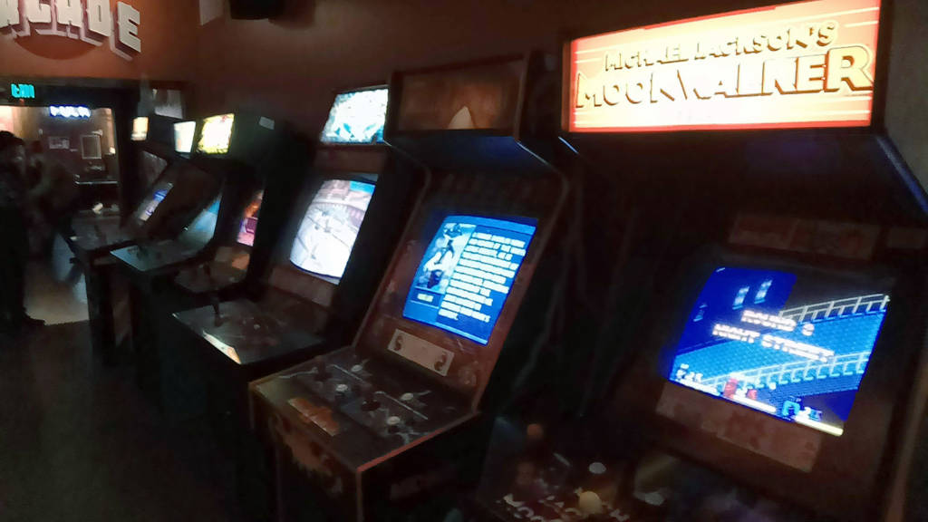 There is a long row of video games on the left side of the bar leading into the arcade