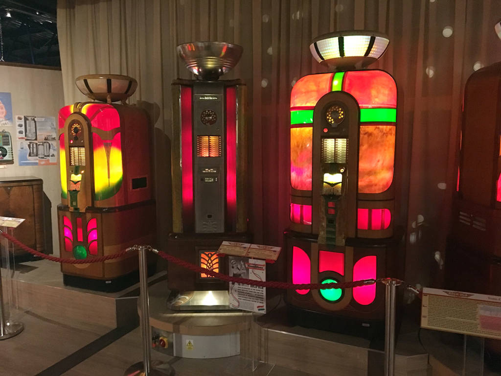 Brightly-coloured jukeboxes on display include the Rock Ola Tone Column